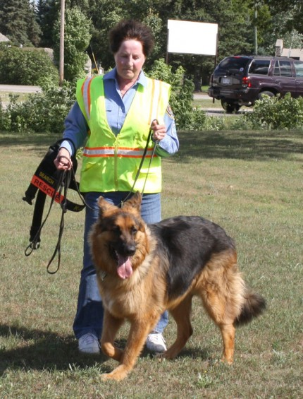 Geri Dault, an Alpena resident and member of the PR team for Search and Rescue of Michigan, works with Koda, a search and rescue dog, during the demonstration.