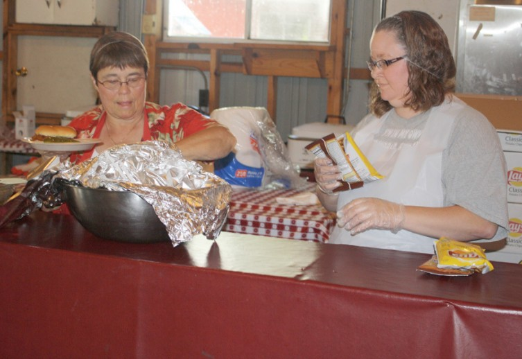 Volunteers Kathy Hodge, at left, and Elizabeth Hawley help to prepare lunch for guests at the fairgrounds. The Mio Moose Lodge organized the lunch.