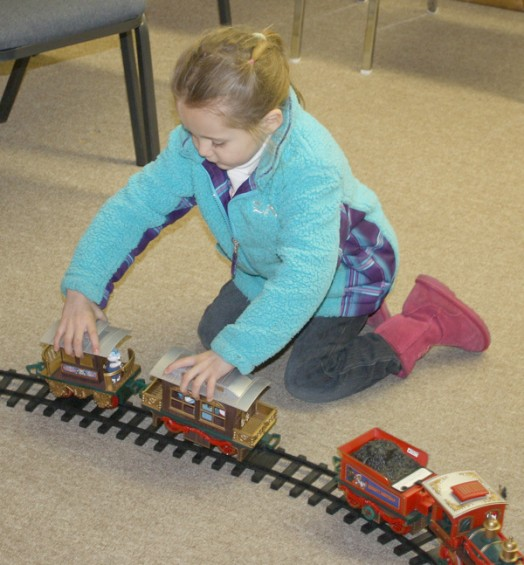 Madison Bondie, 4, of Rose City, tries to put together the cars of a toy train while visiting the American Physical Therapy office in Fairview.