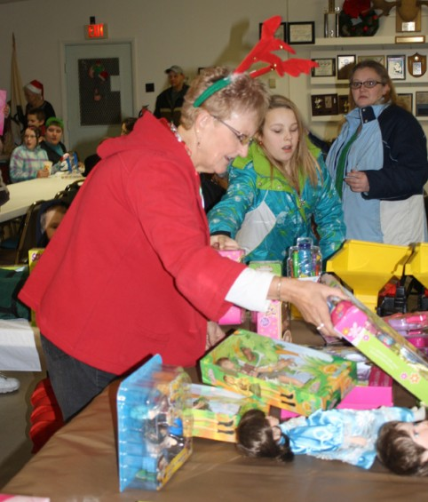 Linda Bowman, one of the Women of the Moose, looks through the toys available to the children at the party.
