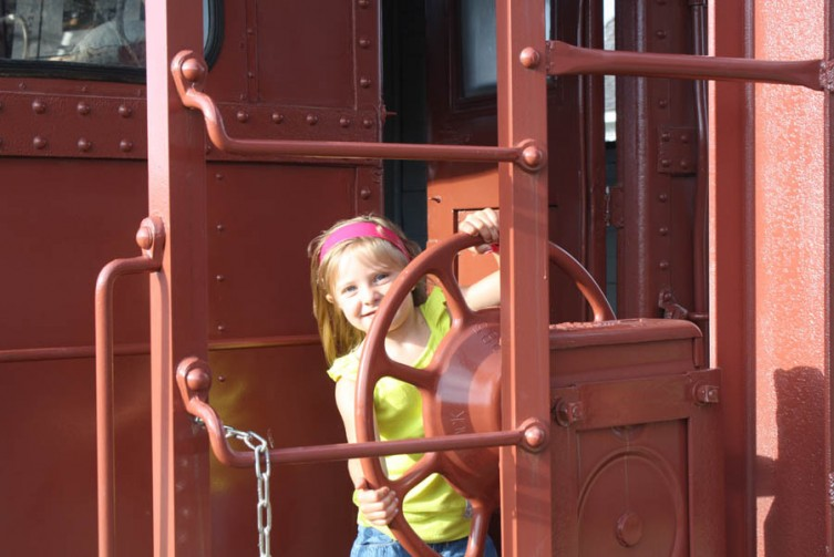 Kennedy Cohee, 3, of Sterling plays on a 1929 caboose while the concert plays.
