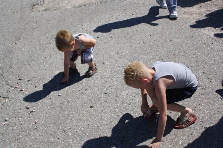 From left, Jayden Handrich, 3, and Alex Handrich, 7, scoop up some candy.