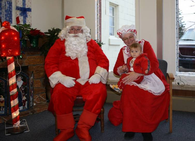 Grail Basil, 9-and-a-half months, of Mio sits on Mrs. Claus' lap during Santa's visit to American Physical Therapy Saturday night before the Holiday Light Parade in downtown Mio.