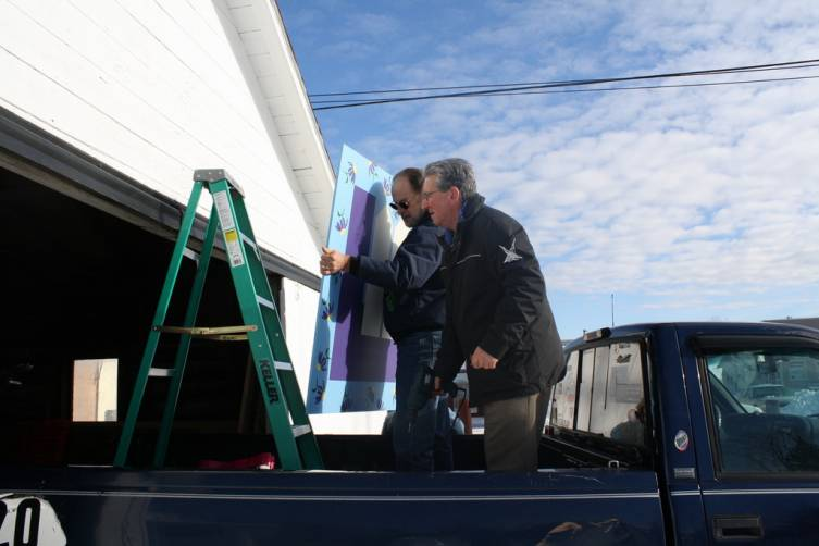 Tim Jenks and Lydia's Gate Emergency Shelter Director Chris Overley prepare to hang a quilt block on the shelter's garage Tuesday.