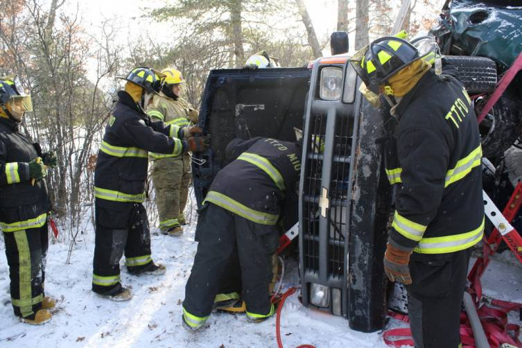 """Firefighters remove the hood of a truck before cutting the roof off to extricate the """"victims."""""""