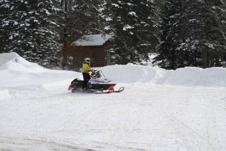 Makala Lawe, 11, of Mio rides a snowmobile around in the snow Feb. 8.