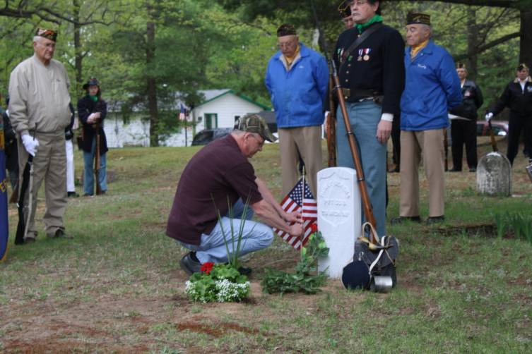 Mike Unger, great-great-grandson of Civil War veteran Henry Serens, plants a flag at the site of his ancestor's new grave marker.