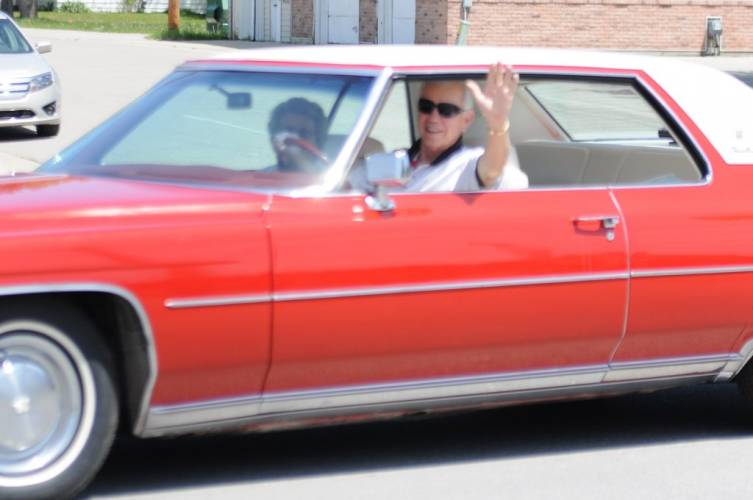 AuGres' Lavern Dittenber waves to the people lining the streets.