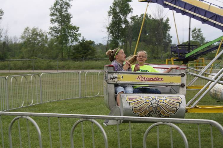 Hailey Powell and Allison Hartman of Standish take a ride on the Scrambler at the county fair.