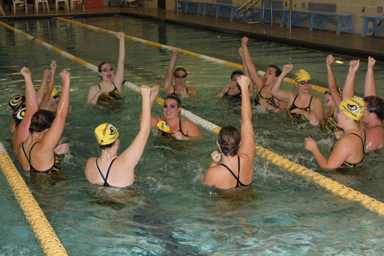 The Ogemaw Heights girls swim team chants a cheer in the pool to get pumped up for the meet.