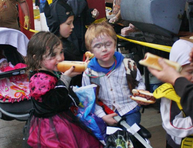 Twins Atreyu and Angellaya Burden, 4, of Mio enjoy free hot dogs provided by the Mio Dummy Club while taking a break from Trick or Treating in downtown Mio Oct. 31.