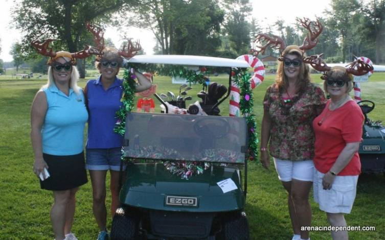 Denise Schutte, Karen McGuire, Nancy Selle and Deb Morgan don reindeer antlers and pose for a photo alongside their decorated cart.