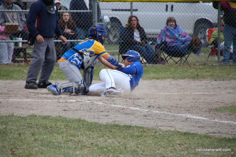 Mio Junior Garrett Rhoads gets an out at home plate.