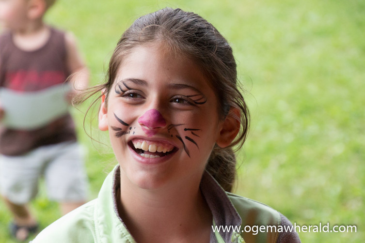Olivia Trevarrow smiles at her mother with her new cat face paint.