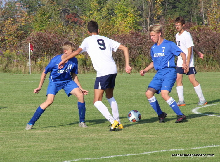 SSC's Carlos Jansa Quiles uses the side of this foot to send a pass to Caden Wooten (11) between two Oscoda defenders.