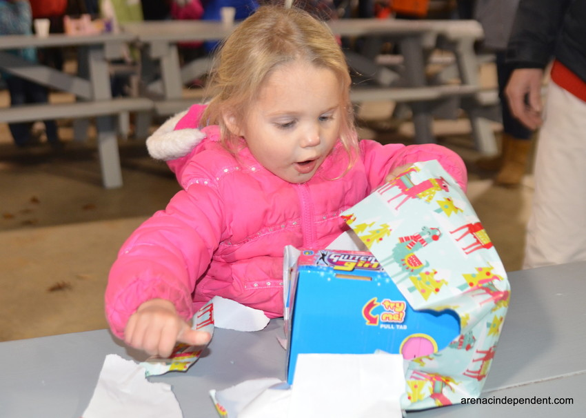 Three year old Katazyna Packard opens her gift with excitement during the 2017 event.