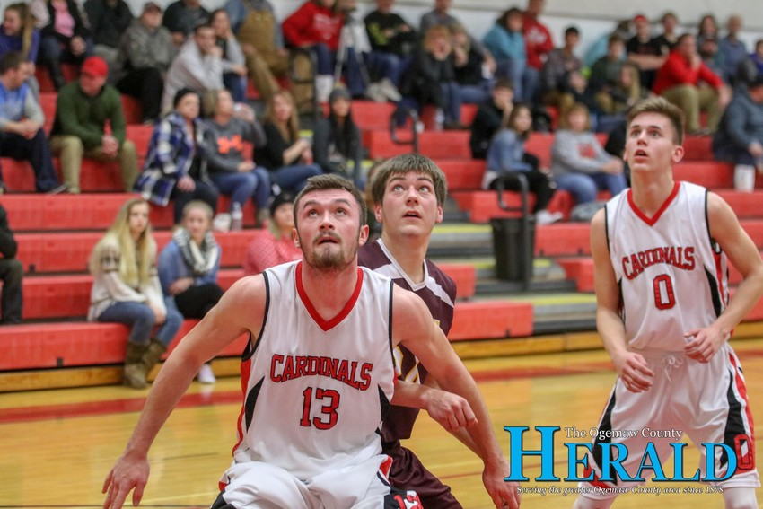 Whittemore's Kyle Colton boxes out Fairview's Jesse Yoder during a Fairview free throw.