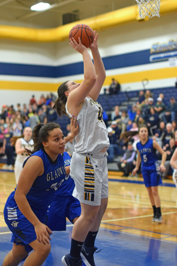 Elle Adrian puts the ball in despite pressure from Gladwin's Kiya Lovett (30).