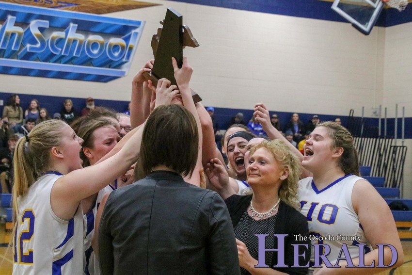 The Mio girls basketball team hoists the district championship trophy in the air after topping Hale.