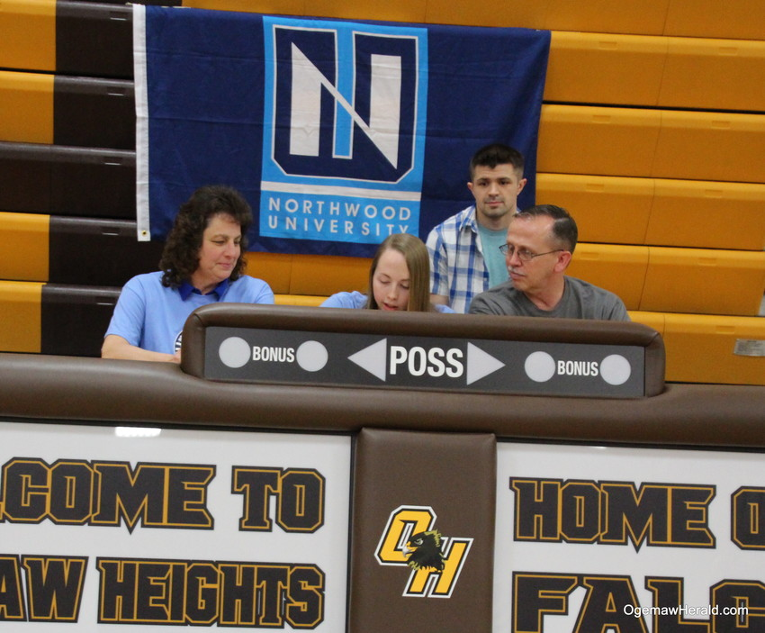 Nicole signs her letter of intent as her mother Jan, father Greg and brother Gregory Jr.