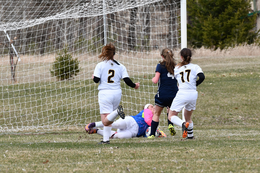 Falcon keeper Sophia Courtemanche dives on the ball that Roscommon's Peyton Church (4) shot on goal.