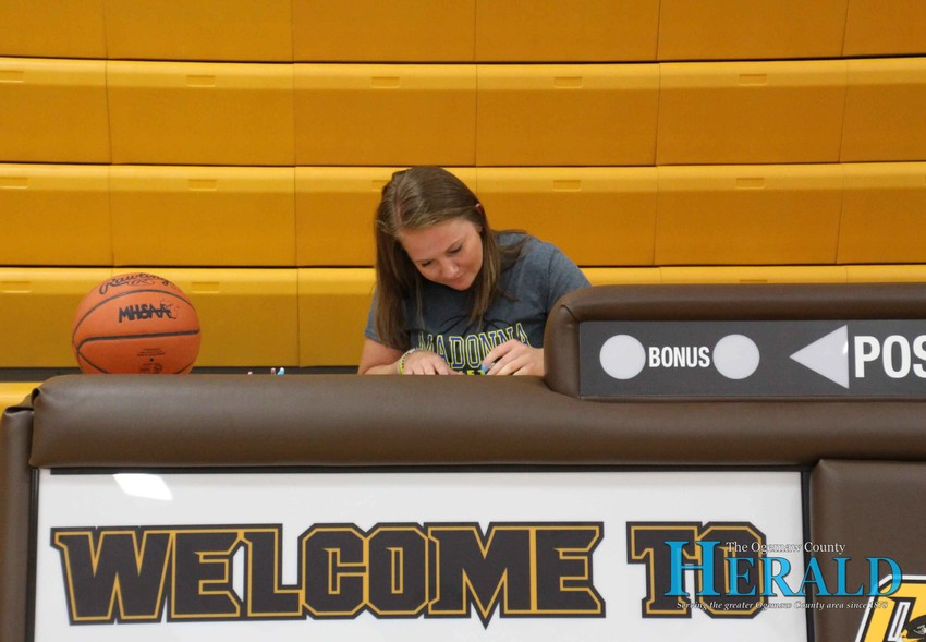 Payton Izworski signs her letter of intent to play basketball with Madonna University.