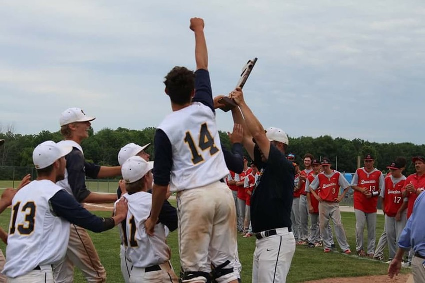 The Standish-Sterling Central baseball team celebrates with the trophy after winning the regional championship Saturday.