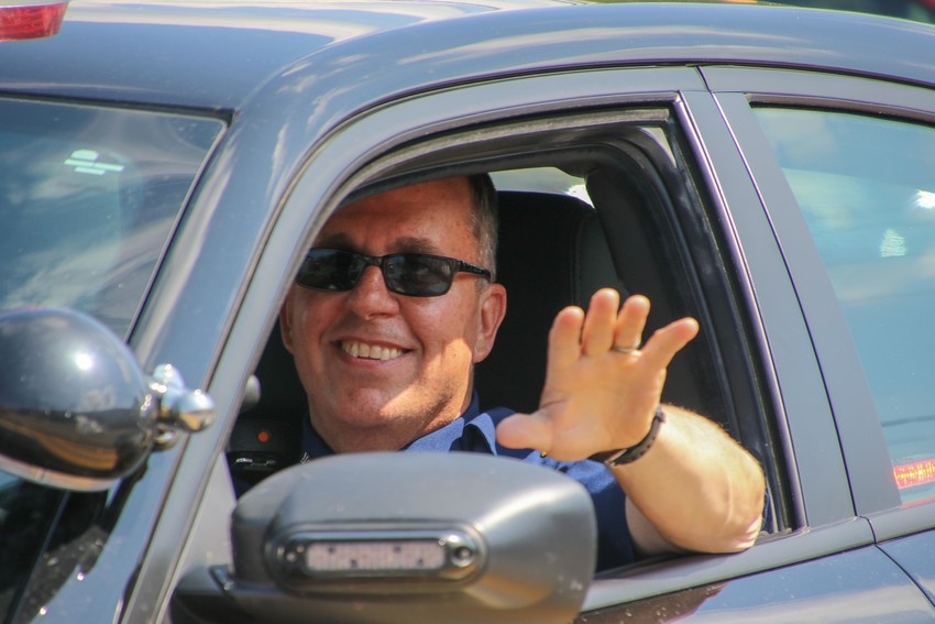 Michigan State Police Sgt. Pete McNamara waves as he rides along in the parade.