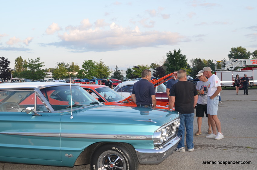 Car enthusiasts chat and admire the many cars parked at the Au Gres city park Satyurday evening after the annual cruise.