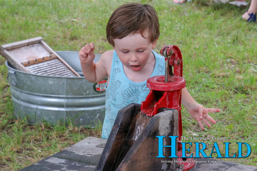 """Leo Barber, 2, """"wows"""" as he watches water flow from a hand pump."""