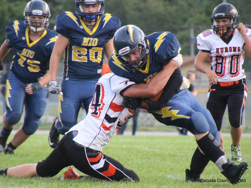 Ben Diller lowers his shoulders and runs over a Rogers City player.