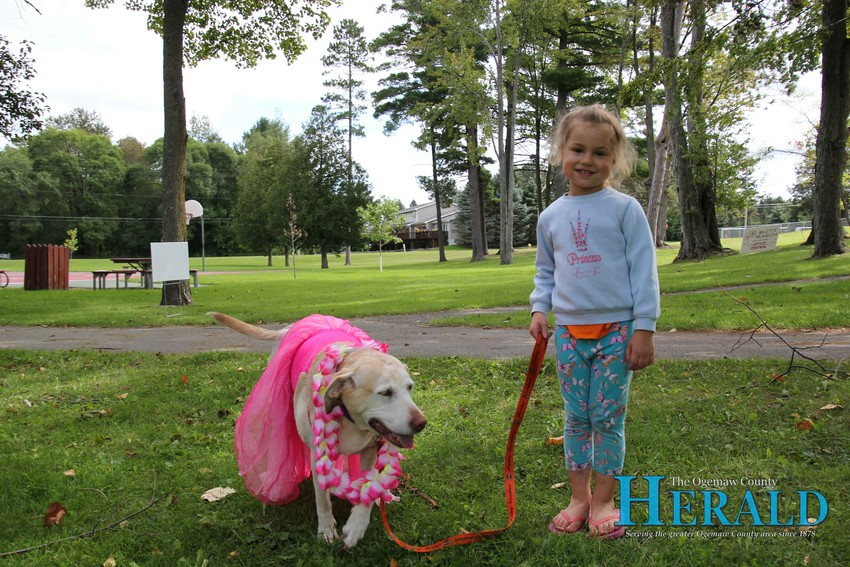 Mia the dog walks with Emma Grell, 4, at the Ogemaw County Humane Society's annual Mutt March at Irons Park Sept. 8