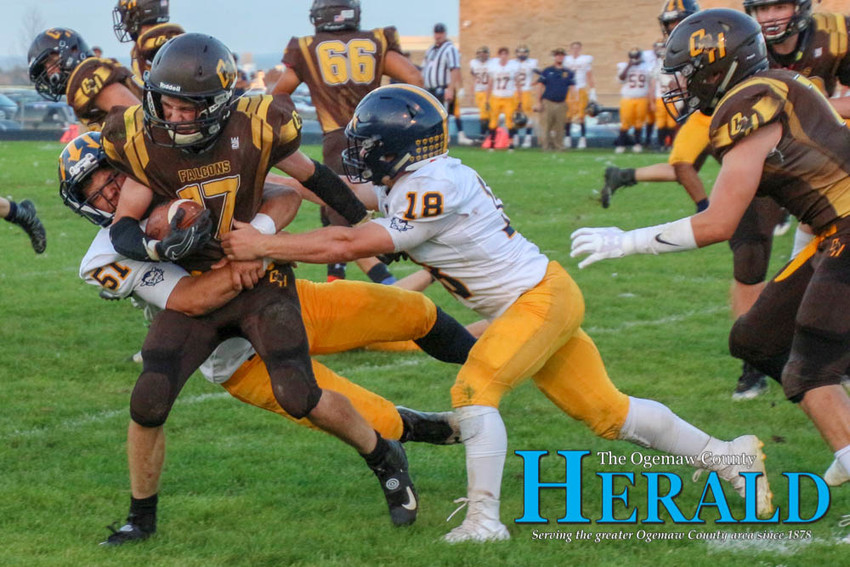 Jony Moore tries to power through being tackled by two Gaylord players.