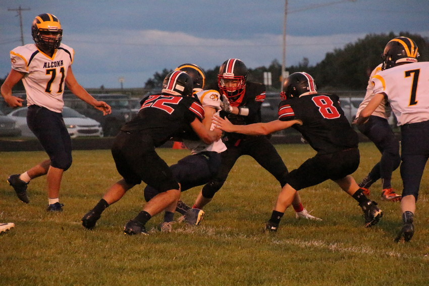 Ridge Schutte (22), Tanner Harrison (2) and Dakota Marr (8) lunge at Tigers running back with the ball.