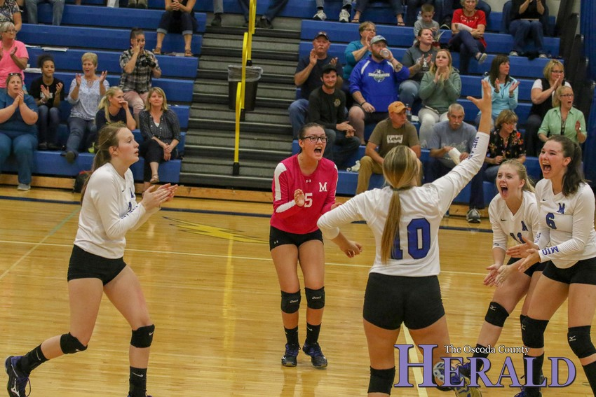 The Mio volleyball team celebrates scoring a point against Rogers City.