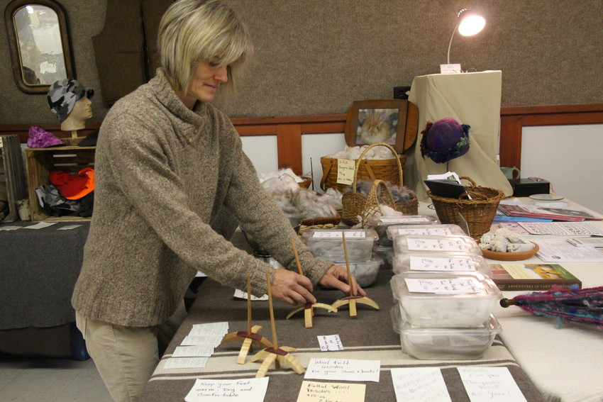 Chris Deshler of Two Tracks Outdoors arranges rabbit wool and items made by her husband Chuck, who makes bows and Turkish drop spindles.