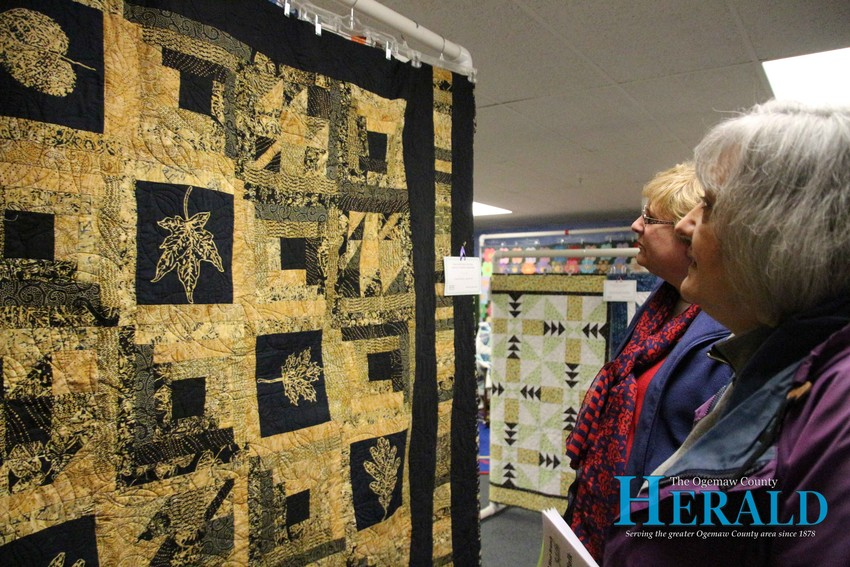 Lil Pandza of West Bloomfield and Lil Pandza of West Branch look at a quilt.