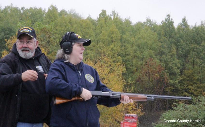 Al Chaney helps Amy Knepp with a shotgun.