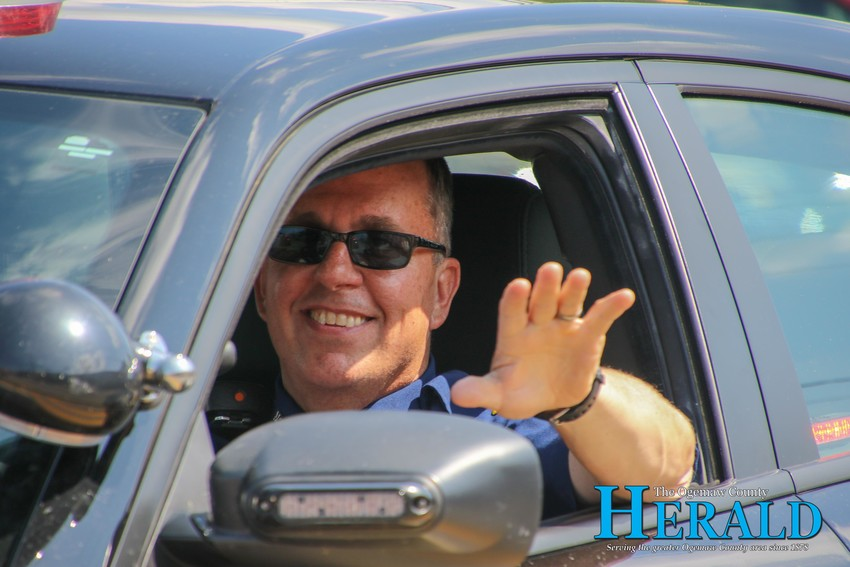 Michigan State Police Sgt. Pete McNamara waves as he rides along in the Rose City Fourth of July parade.