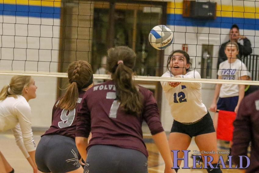 Mio's Madison Barron bumps the ball as her AGS opponents look on.