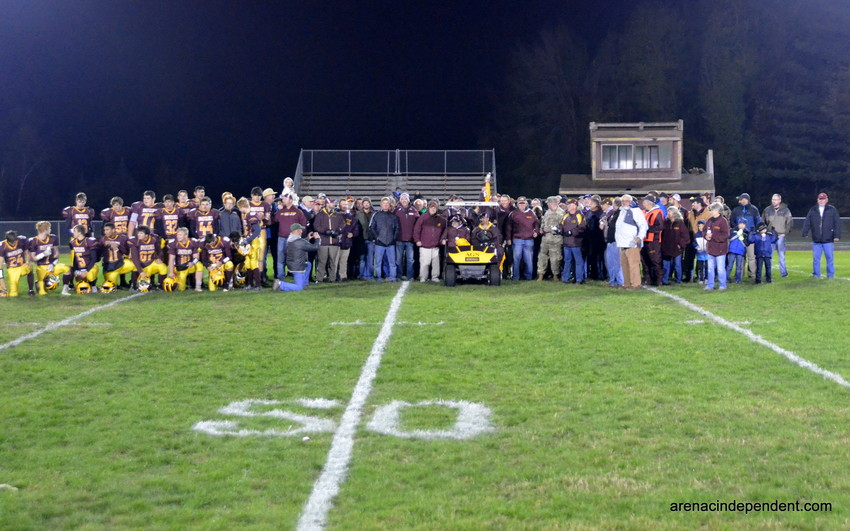 Au Gres celebrates with past and present football players and coaches during halftime.
