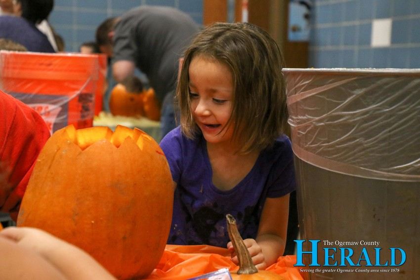 Alicia Sikorski, 5, concentrates as she decorates her pumpkin.