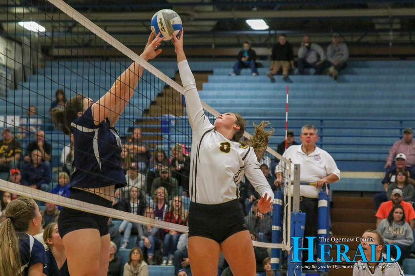 Ogemaw's Faith Ignasiak and Standish-Sterling's Elle Adrian battle for the ball above the net as Ignasiak tries to tip it over.