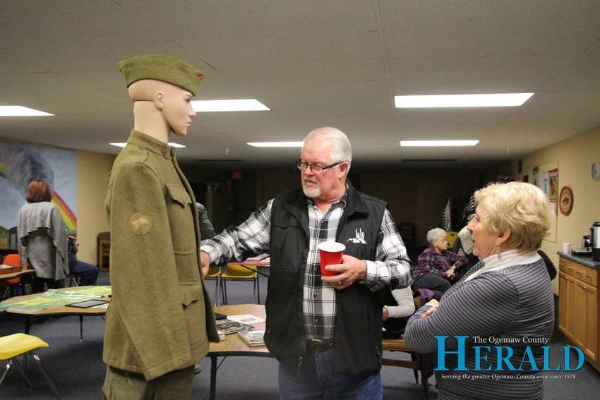 Local veteran John Bennett and Joyce Nelander look at a World War I uniform that belonged to Ira Glen Curtis.