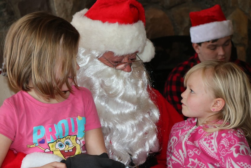 Catherine and Sydney Cook sit on Santa's lap during last year's Alger Children's Christmas Party.
