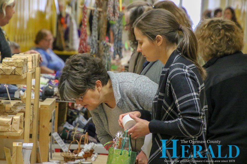 Sarah Bruder and Amy Mason of West Branch check out some of the Christmas candles for sale.