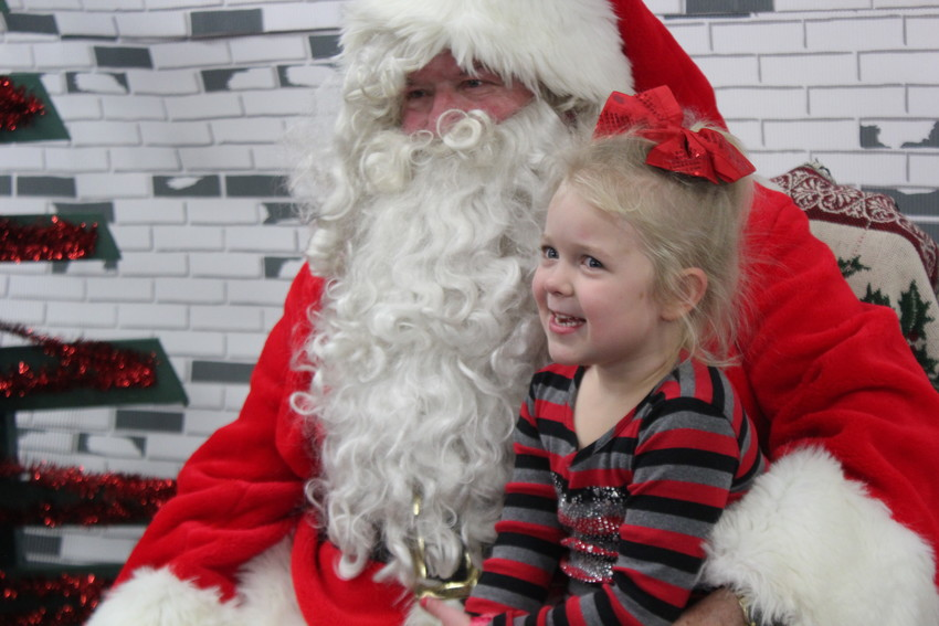 Five-year-old Adelyn Damron's face lights up as she sits on Santa's lap.