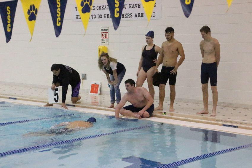 The team sits on one end of the pool to cheer on their fellow Panther.