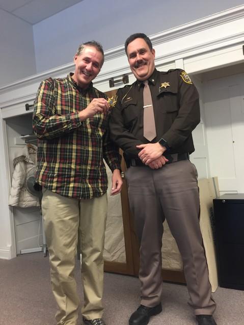 Former Sgt. Chuck Varner and Sheriff Kevin Grace smile together after Varner is awarded the badge.