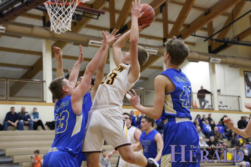 Fairview's Nathaniel Eastman shoots and scores a basket as his Mio opponents attempt to block him.